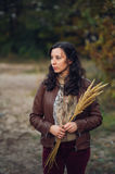 Pensive woman with bunch from autumn plant in hands Royalty Free Stock Photos