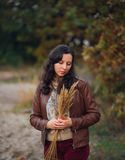 Pensive woman with bunch from autumn plant in hands Stock Image
