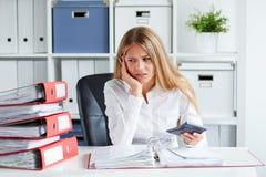 Pensive woman calculates taxes. Pensive business woman calculates taxes at desk in office Royalty Free Stock Photos