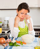 Pensive woman cooks rice with vegetables Stock Photography