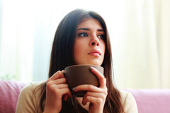 Pensive woman with cup of coffee looking away Royalty Free Stock Images