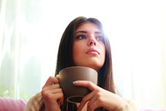 Pensive woman with cup of coffee looking away Stock Photo