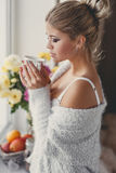 Pensive woman with a cup of hot tea Stock Image