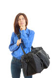 Pensive woman daydreaming going on vacation with travel bag Royalty Free Stock Image