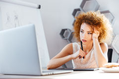 Pensive woman designer using laptop and grapic tablet on workplace Stock Images