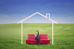 Pensive woman in dream house outdoor Stock Photo