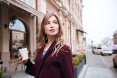 Pensive woman drinking coffe on the street of the city Royalty Free Stock Photo