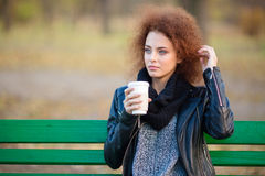 Pensive woman drinking coffee outdoors Stock Image