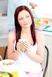 Pensive woman eating her breakfast holding coffee Royalty Free Stock Photos