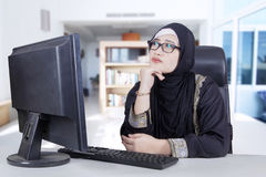 Pensive woman in front of computer. Arabian businesswoman wearing glasses sitting in the living room while daydreaming with computer Stock Image