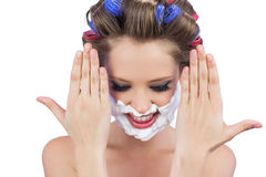 Pensive woman with hands up and shaving foam on face Stock Images