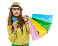 Pensive woman in hat with shopping bags and credit card Royalty Free Stock Photo