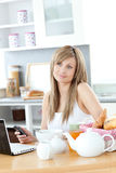 Pensive woman having breakfast using laptop Stock Photography