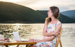 Pensive woman having with computer by the lake Stock Photos
