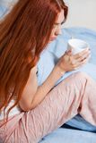 Pensive Woman Having an Early Coffee at her Bed Stock Images