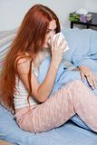 Pensive Woman Having an Early Coffee at her Bed Stock Image