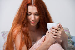 Pensive Woman Having an Early Coffee at her Bed Royalty Free Stock Photo