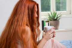 Pensive Woman Having an Early Coffee at her Bed Royalty Free Stock Images
