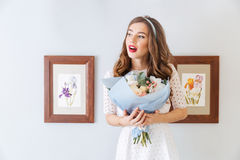 Pensive woman holding bouquet of flowers Royalty Free Stock Photos