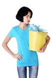 Pensive woman holding bucket of plastic rubbish.  stock photo
