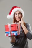 Pensive woman holding Christmas gifts Stock Photography