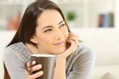 Pensive woman holding a coffee cup looking at side Royalty Free Stock Photography