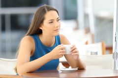Pensive woman holding a coffee mug in a bar. Single pensive woman alone holding a coffee mug sitting in a bar royalty free stock images