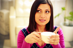 Pensive woman holding cup of coffee Stock Photos