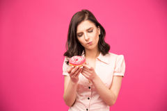 Pensive woman holding donut Royalty Free Stock Photo