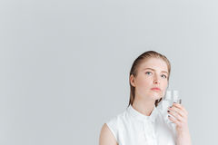 Pensive woman holding glass of water Royalty Free Stock Photos