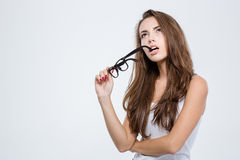 Pensive woman holding glasses and looking up Stock Image