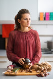 Pensive woman holding a jar of mushrooms in kitchen Royalty Free Stock Image