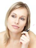 Pensive woman holding lipstick Stock Photo