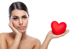 Pensive woman holding red heart Stock Images