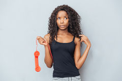 Pensive woman holding retro phone tube and looking away Royalty Free Stock Images