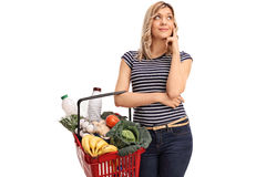 Pensive woman holding a shopping basket. Pensive young woman holding a shopping basket isolated on white background Royalty Free Stock Photography