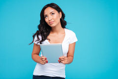 Pensive woman holding tablet computer and looking up Stock Images