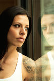 Pensive woman at home looking by the window Royalty Free Stock Images