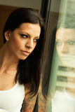 Pensive woman at home looking by the window Stock Image