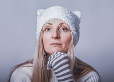 Pensive woman with intent look in funny hat with ears and striped gloves look calm at camera, close-up royalty free stock image