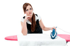 Pensive woman ironing things to wear Royalty Free Stock Photos