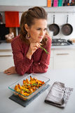 Pensive woman at kitchen counter with closeup of pumpkin Royalty Free Stock Images