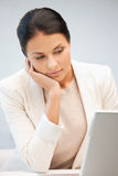 Pensive woman with laptop computer Royalty Free Stock Photos