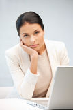 Pensive woman with laptop computer Stock Photos