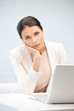 Pensive woman with laptop computer Stock Image
