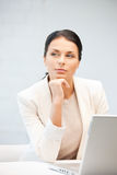 Pensive woman with laptop computer Stock Photo