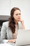Pensive woman with laptop computer Royalty Free Stock Image