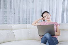 Pensive woman with laptop at home Stock Images