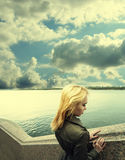 Pensive woman leaning on granite sea-wall ander sky with clouds Stock Photography
