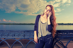 Pensive woman listening to the cell phone in front of waterfront fence Stock Photography